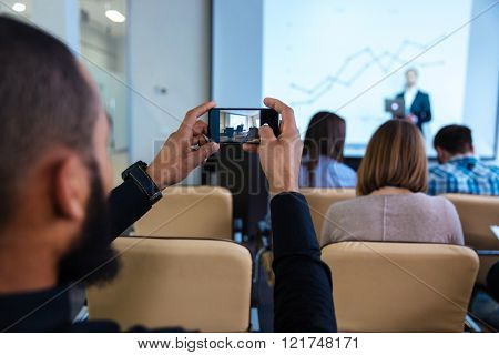 Back view of young african man making video with smartphone on business conference in meeting room