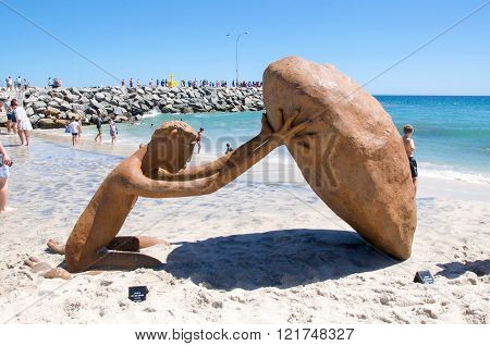 COTTESLOE,WA,AUSTRALIA-MARCH 12,2016:  Human stone figure sculpture with tourists at the interactive free public arts festival