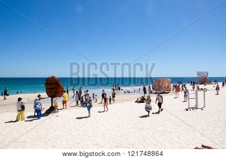 COTTESLOE,WA,AUSTRALIA-MARCH 12,2016:  People walking the beach viewing sculptures at the interactive free public arts festival