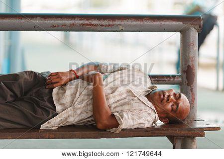 BANGKOK, THAILAND, JULY 29, 2013 : A homeless mature man is sleeping on a bench in Bangkok, Thailand.