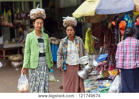 AMARAPURA, MYANMAR, JANUARY 17, 2015 : Two women are carrying bags with galangal roots on their heads, walking in the street of the Zegyo market, in Mandalay, Myanmar (Burma).
