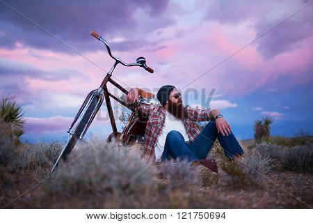cool bearded guy with bike in the desert sitting on suitcase