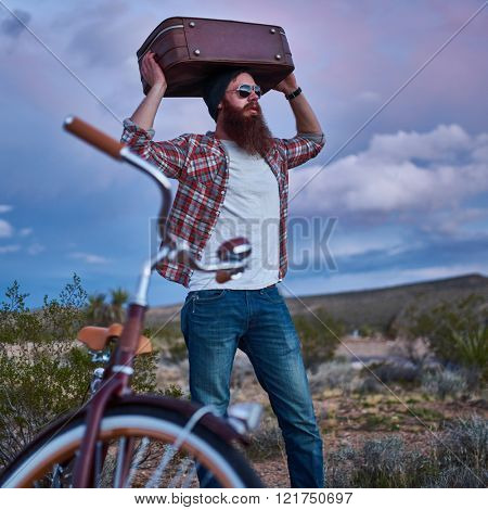 bearded traveler with suitcase overhead and bike in desert