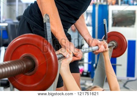 Woman working his arms and chest at gym. She lifting barbell. Man keeps barbell in sport gym.