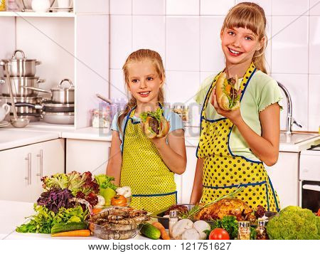 Children little girl cooking on their own at kitchen. Cooking food in  kitchen.