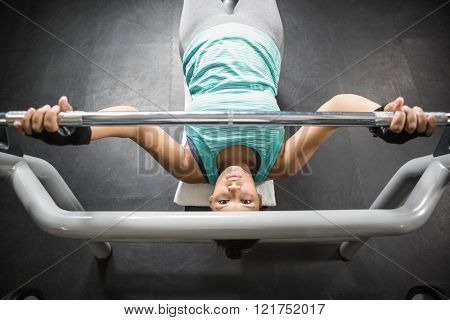 Woman using weight machines in the gym to train arms