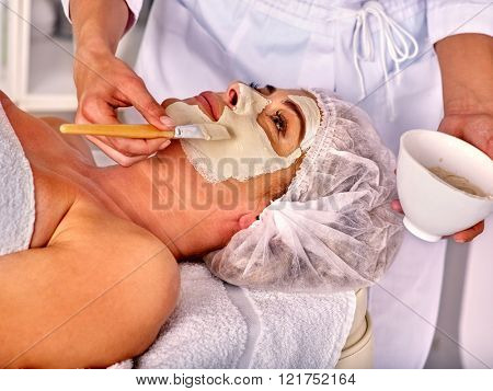 Woman middle-aged take facial and neck clay mask in spa salon. Facial mask.
