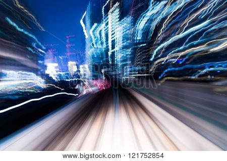Speedy train passing though in city at night