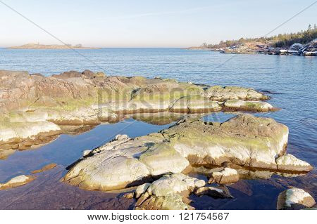Archipelago sea and rocks covered with green algae a sunny morning in spring in Sweden