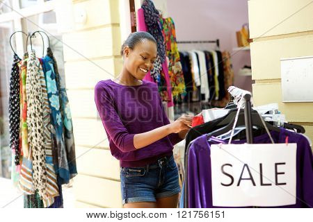 Portrait of happy young african american woman shopping for clothes at store