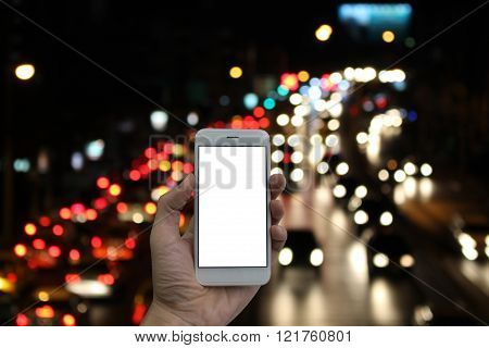 Man holding a smart phone screen blank, blurred traffic jam