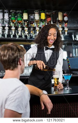 Barmaid pouring beer into beer glass for serving a man at bar counter in bar