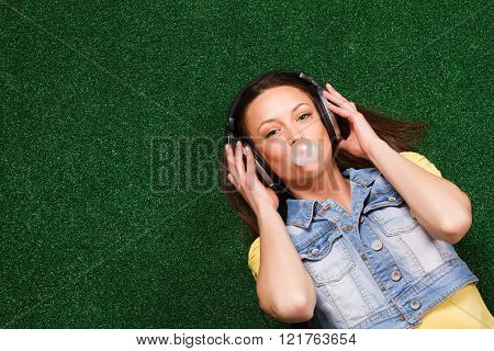 Woman listening music and blowing bubble