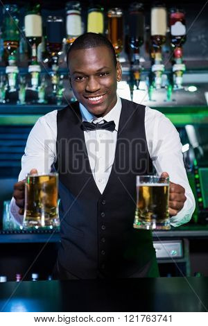 Bartender serving two glasses of beer at bar counter in bar
