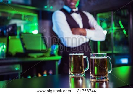 Two glasses of beer on bar counter and bartender standing in background