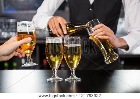 Bartender serving beer at bar counter in bar