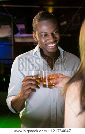 Man smiling while toasting his whisky glass in bar