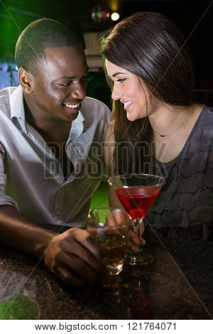 Couple looking at each other and smiling while having drinks at bar