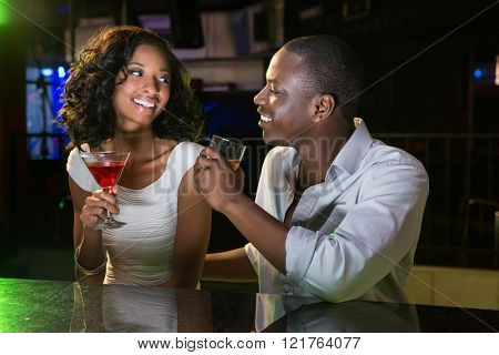 Couple talking and smiling while having drinks at bar counter in bar