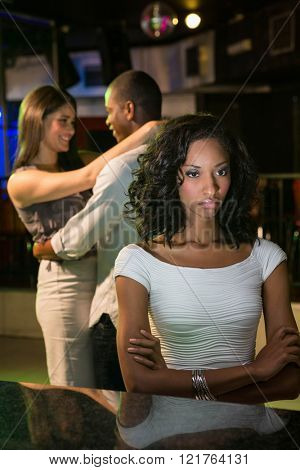 Unhappy woman sitting at bar counter and couple dancing behind her in bar