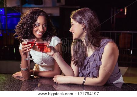 Young women toasting cocktail glasses at bar counter in bar