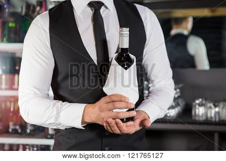 Mid section of bartender holding a wine bottle in bar