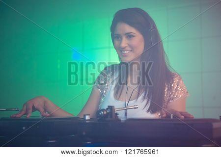 Pretty female DJ playing music at the nightclub