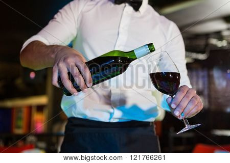 Waiter pouring wine in a glass in bar