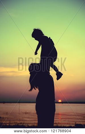 Silhouette of mother and child enjoying the view at riverside. Mother lifting her little girl up in the air on colorful sunset sky background. Friendly family. Cross process. Vintage style.