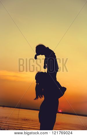 Silhouette of mother and child enjoying the view at riverside. Mother lifting her little girl up in the air on colorful sunset sky background. Friendly family.