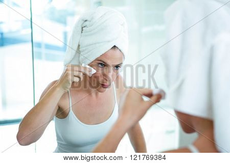 woman using a cotton pad to clean her skin in the mirror