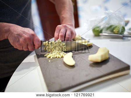 Man cooking at home, chopping ginger for a recipe ** Note: Visible grain at 100%, best at smaller sizes