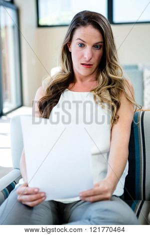 shocked woman sitting on the couch reading papers