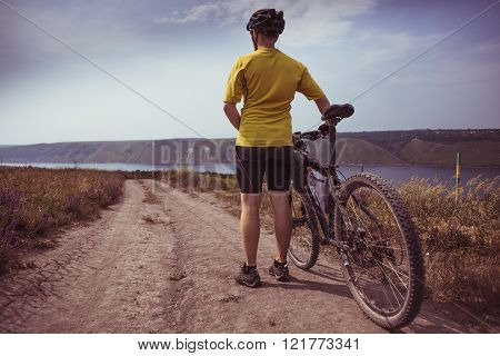 Young bicyclist relax in beautiful nature near river. Hot sunny summer day