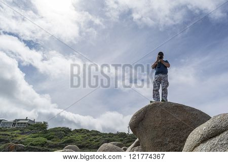 Horseshoe Bay, South Australia, Australia - 12 Mar 2016: A male photographer taking a photo from the top of the boulders at Horseshoe Bay, South Australia