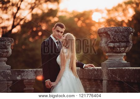 Beautiful romantic wedding couple, groom and bride hugging near old castle on sunset