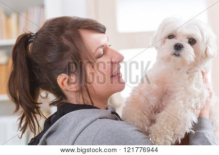 Young, smiling woman wearing deaf aid and holding her little dog
