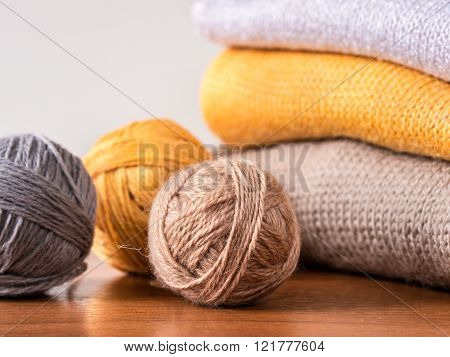 yarn and knitwear on wooden table