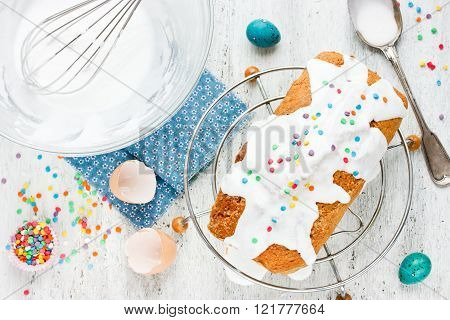 Easter Cake With White Icing And Colorful Sprinkling On A White Table