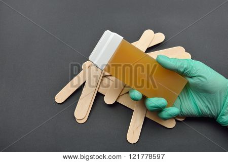 Beauticians Hand With Green Glove Holding A Roll On Liposoluble Wax Cartridges From Honey For Waxing
