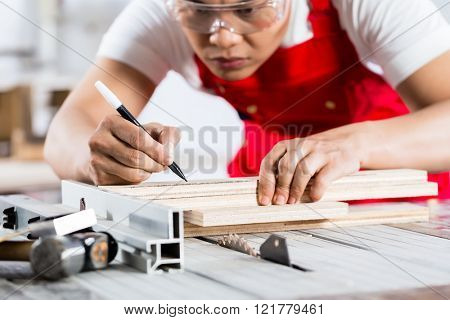 Asian Chinese Carpenter cutting wood with circular saw in his workshop