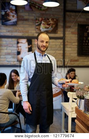 Waiter working in cafeteria, holding plates, looking at camera.