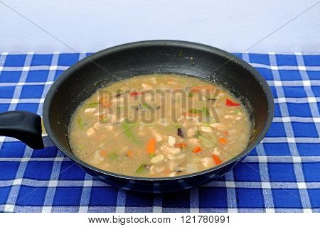 Chinese delicate sauce with beans carrots meat in the pan on a placemat with blue cubes