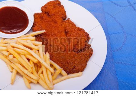 Breaded cutlets with french fries and ketchup