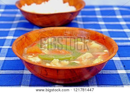 Chinese delicate sauce with beans carrots meat in a wooden bowl on a placemat with blue cubes