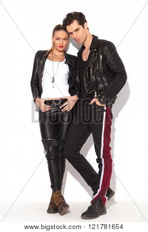 rock and roll couple in leather clothes standing together against white wall
