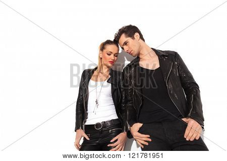 young sexy couple in leather clothes standing next to each other with hands in pockets