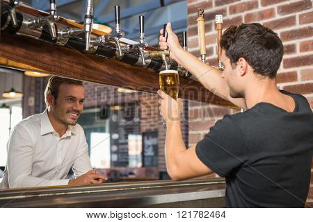 Handsome bar tender pouring a pint for a customer in a pub