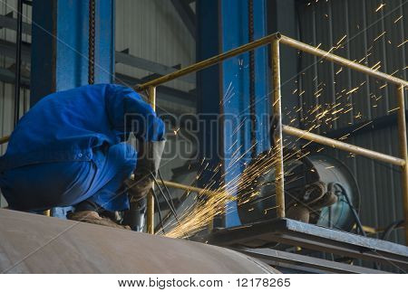 Workman using grinder in workshop