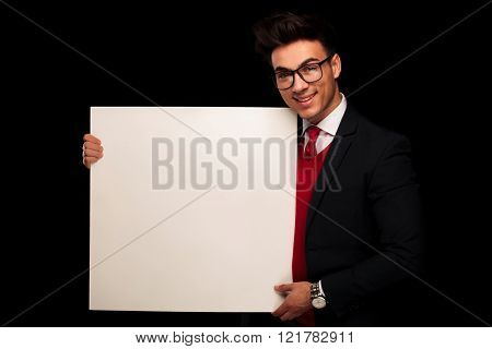 portrait of classy model in black suit wearing glasses while presenting a blank billboard and looking at the camera in dark studio background
